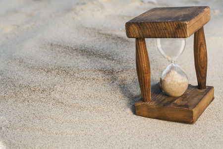 Vintage hourglass in the sand with small shadow photo