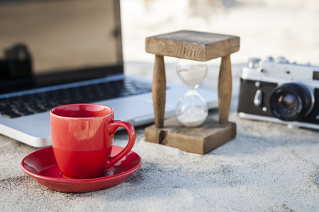 Red Coffe Mug and Vintage hourglass with silver laptop and old camera in the sand at the beach photo
