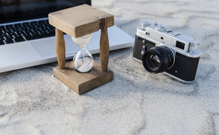 Vintage hourglass with silver laptop and old camera in the sand at the beach photo