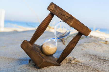 Old wooden houglass in sand on the beach with the sea and blue sky in the background photo