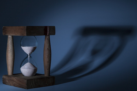 timeless: Wood old brown Hourglass with blue lightning with shadow Stock Photo