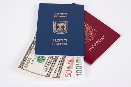Israeli and Romanian passports with dollar and euro banknotes isolated on white photo