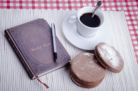 Old notbook closed with fountain pen round cookies and cup of coffee on white wood background photo