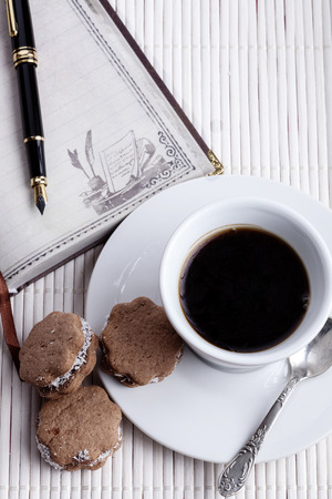 brown cookies with coffee in a white mug and silver spoon with fountainpen and old notebook on white wood background photo