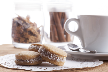 Small round cocnut cookies with white coffee mug in the bakcground on wooden plate photo