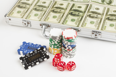Casino chips with red dice and briefcase full with dollars isolated on white background photo