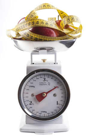 Red apple with  yellow measuring tape on kitchen scale isolated on white photo
