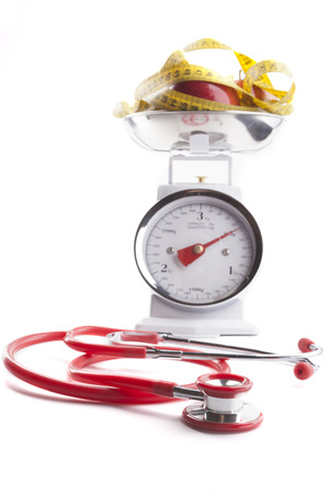 Red stethoscope with Red apple and  yellow measuring tape on kitchen scale isolated on white photo