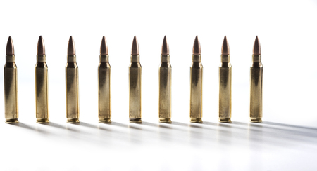 Row of shiny rifle bullets isolated on white with shadows photo