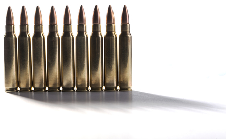 Row of shiny rifle bullets standing together isolated on white with shadows photo