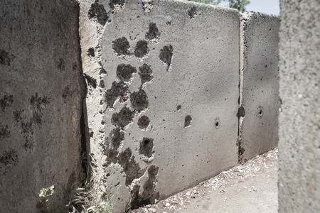 Concrete wall full with old war bullet holes photo