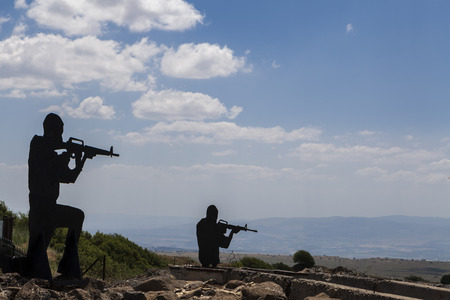 Two Soldiers silhouetts with blue sky in the background and rock reinforments in the foreground photo