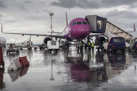 Purple airplane on the ground with maintenance cars around