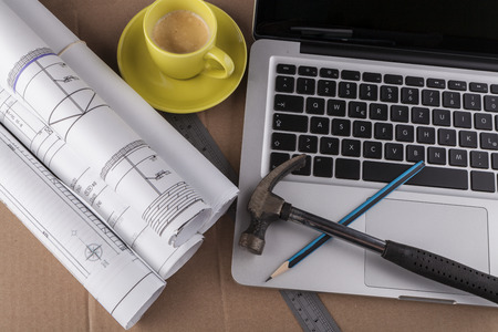 Architectural plans rolled with silver laptop hamer and a pencil photo