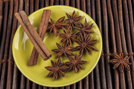 Cinnamon sticks with star shape anis on green plate and wood background photo