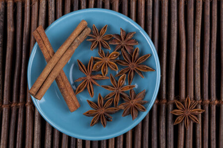Cinnamon sticks with star shape anis on blue plate and wood background photo