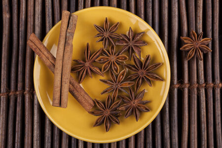 Cinnamon sticks with star shape anis on yellow plate and wood background photo