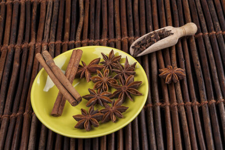 anis: Cinnamon sticks with star shape anis on green plate and wood background