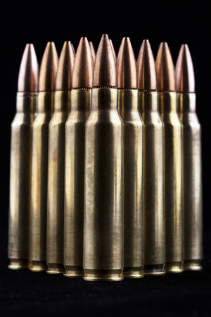 Shiny rifle bullets close-up on black background photo