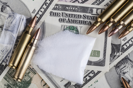 drug deals: Bullets on dollar banknotes with a bag of white drug powder Stock Photo