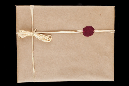 Old brown wrapping paper gift close-up with tied bow and red wax seal photo
