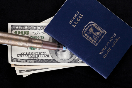 israel passport: Israelian passport with dollar banknotes and a rifle bullet isolated on black background Stock Photo