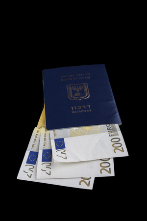 Israelian passport with 200 euro banknotes isolated on black photo