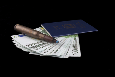 Israelian passport with 100 euro banknotes and a rifle bullet isolated on black background photo