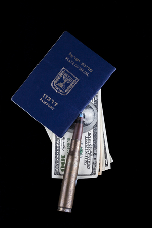 Israelian passport with dollar banknotes and a rifle bullet isolated on black background photo