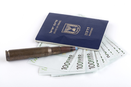 Israelian passport with 100 euro banknotes and a rifle bullet isolated on white background photo