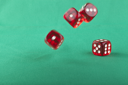 Four red bouncing dice On green background with some shadow photo