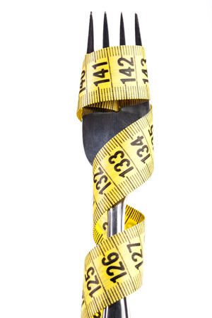 Yellow measuring tape on a fork isolated on white background