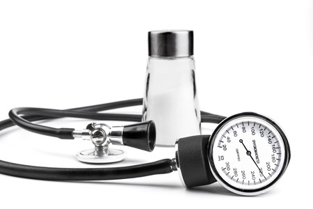 high blood pressure: Salt an blood pressure tools isolated on white background