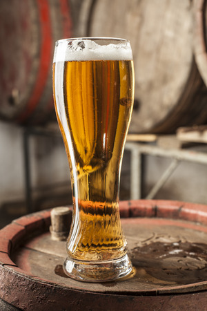 single beer: Single Beer Glass with foam and old wood barrels in the background Stock Photo
