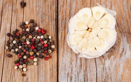 Cut garlic with color pepper spice on old wood textured table photo