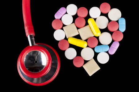 antibiotic pink pill: Heart shape Coloerd pills medicine  on black background with red stehoscope