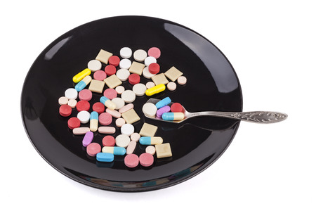 Silver spoon full with  medicine  colored pills in the background photo