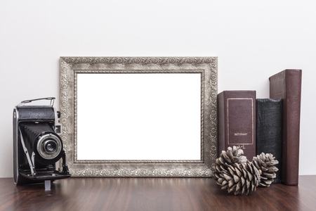 Silver Frame with old books and old camera on wood table