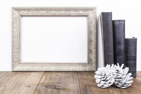 vintage photo frame: Horizontal Silver Frame With Old Books on Brown Wood Table Stock Photo