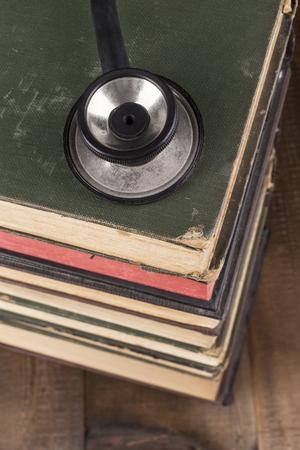auscultate: Black Stethoscope Closeup on Old Books Pile