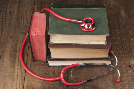 auscultate: Old Books on Wood Table With Red Stethoscope