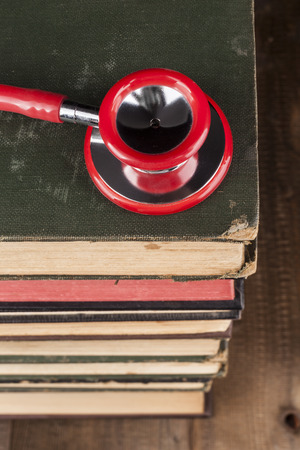 red stethoscope: Red Stethoscope Closeup on Old Books Pile