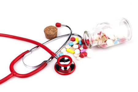 pharmacologist: Red Stethoscope with jar of pills Close-up Isolated On White Background Stock Photo