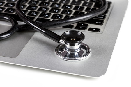 computer technology: Black Stethoscope Closeup On Silver Laptop  With White Background Stock Photo