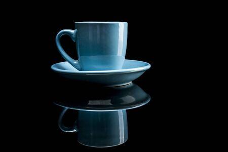 reflexion: Taza de café azul aislado sobre fondo negro con la reflexión
