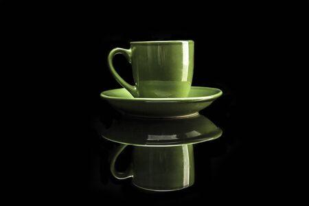 reflexion: Taza verde aislado en el fondo negro con la reflexión Foto de archivo