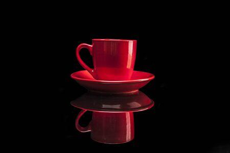 reflexion: Taza roja aislada en el fondo negro con la reflexi�n Foto de archivo