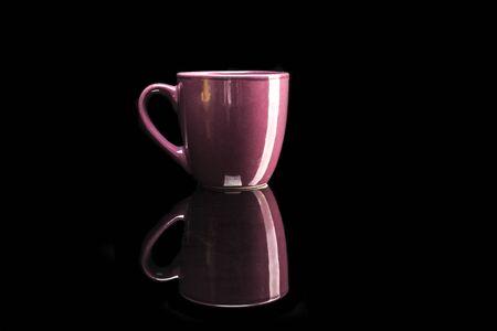 reflexion: taza de color rosa aisladas sobre fondo negro con la reflexión