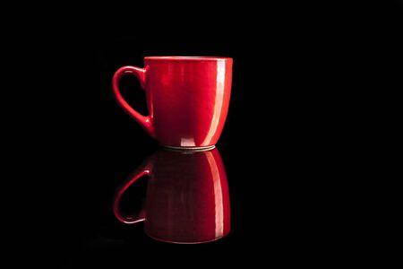 reflexion: Taza roja aislada en el fondo negro con la reflexión Foto de archivo
