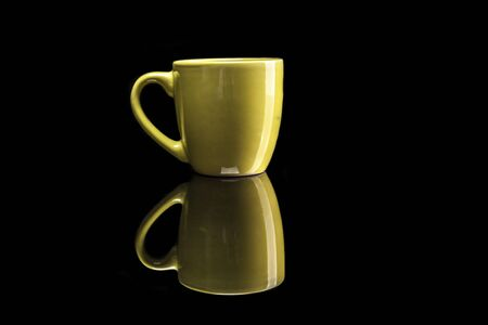 reflexion: Taza amarilla aislada en el fondo negro con la reflexión